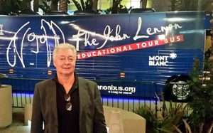 Photo of Alex Ayzin standing in front of John Lennon Educational Bus that travels the United States giving young people a chance to create original music with state of the art instruments and equipment.